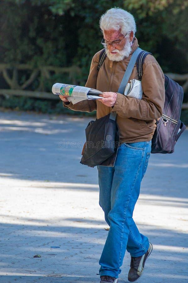 Hombre que camina y que lee el periódico en Campo Grande de Valladolid en septiembre de 2011 fotos de archivo libres de regalías