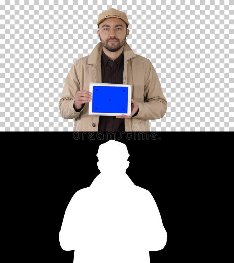 Hombre que camina y que sostiene la tableta con la maqueta de la pantalla azul, Alpha Channel imagenes de archivo
