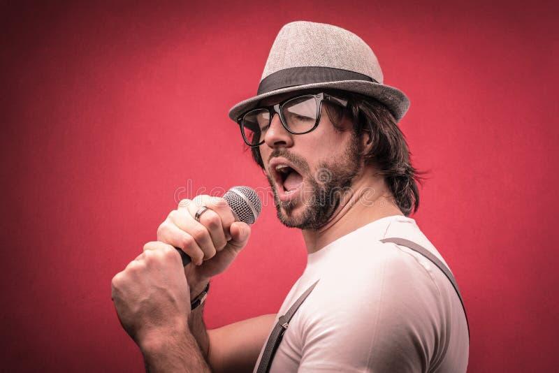 Hombre que canta con un micrófono fotografía de archivo