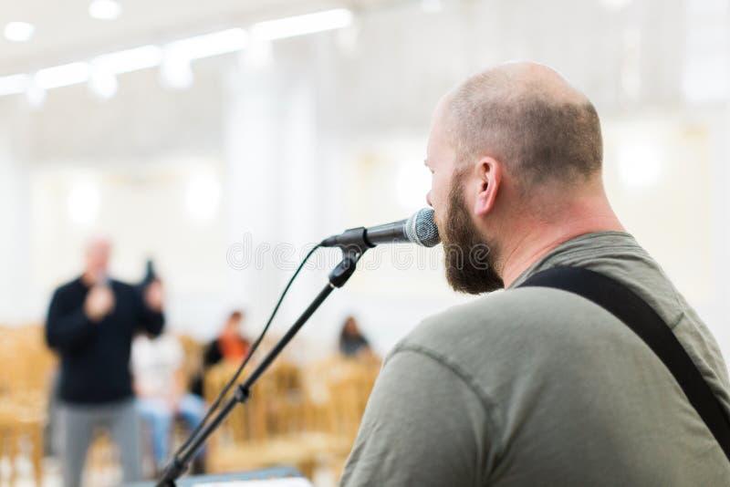 Hombre que canta y que toca la guitarra acústica imagenes de archivo