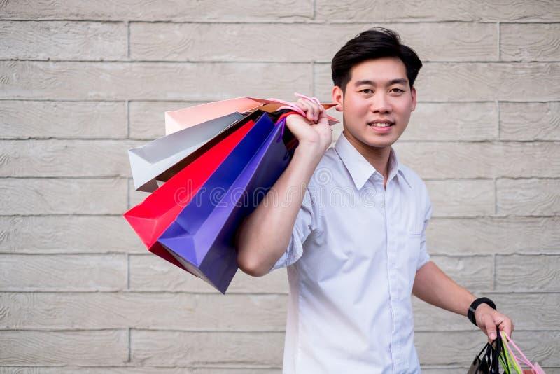 Hombre que celebra mirada del bolso de compras en la cámara y la sonrisa, concepto que hace compras imagen de archivo libre de regalías