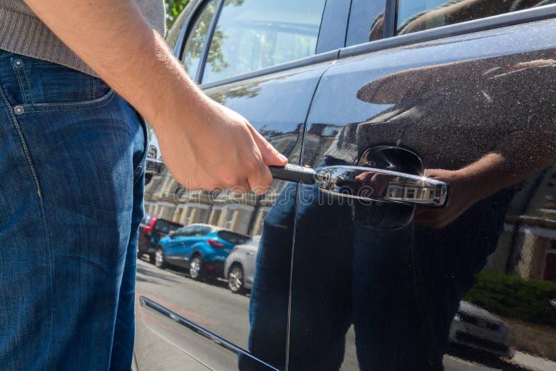 Hombre que cierra o que desbloquea una puerta de coche imagen de archivo libre de regalías