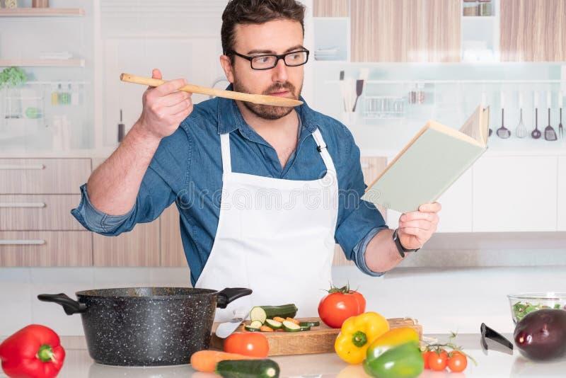 Hombre que cocina en casa la lectura en el libro de la receta foto de archivo libre de regalías