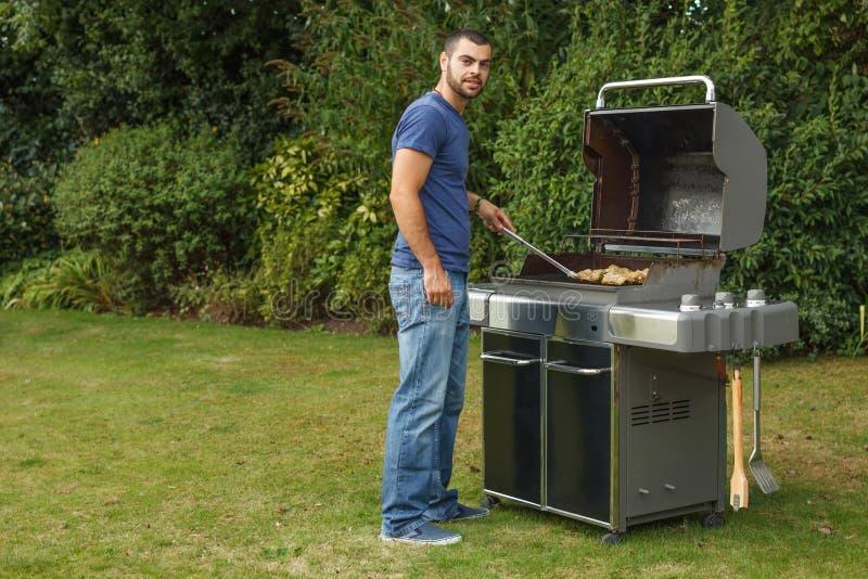 Hombre que cocina la carne imagen de archivo libre de regalías