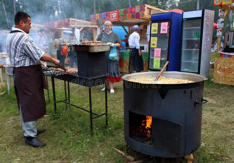 Hombre que cocina la carne adobada fotos de archivo