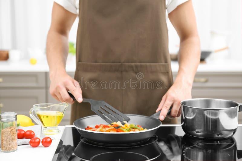 Hombre que cocina verduras en sartén foto de archivo