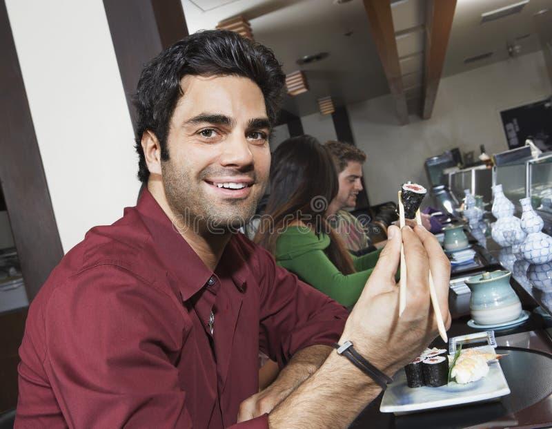 Hombre que come el sushi con los palillos fotografía de archivo libre de regalías