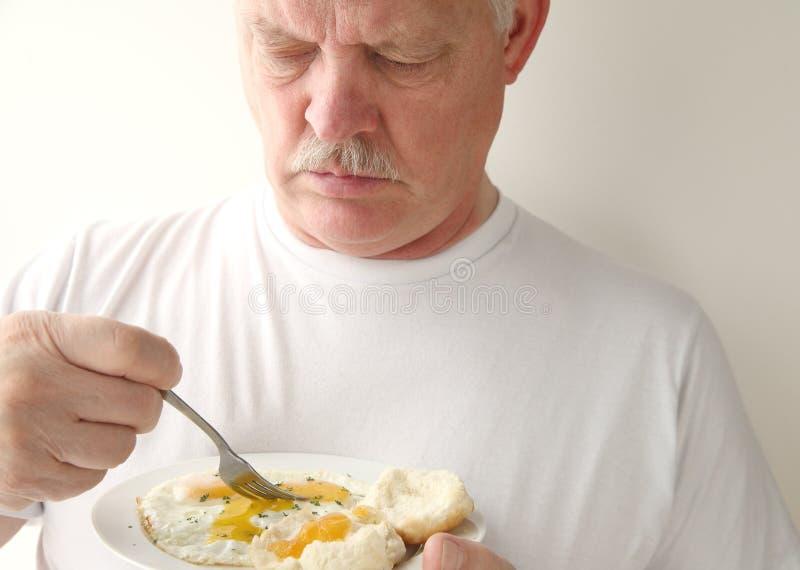 Hombre que come huevos fritos y galletas imagen de archivo libre de regalías