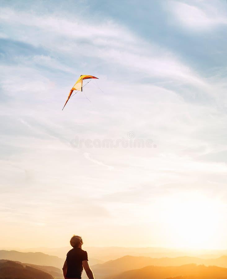 Hombre que comienza a volar la cometa brillante en cielo de la puesta del sol sobre la montaña Imagen de lanzamiento acertada del fotografía de archivo