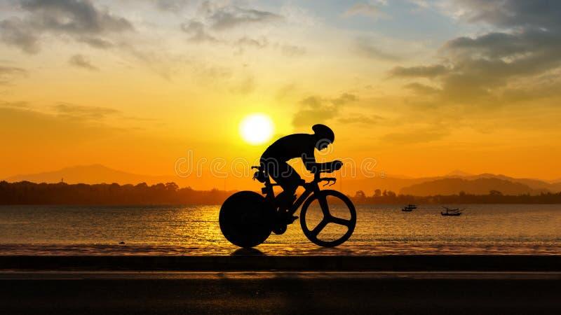 Hombre que completa un ciclo en el tiempo de la tarde de la playa foto de archivo