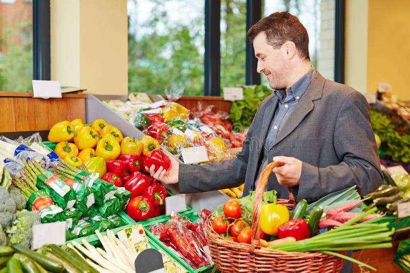 Hombre que compra pimienta roja en supermercado fotos de archivo