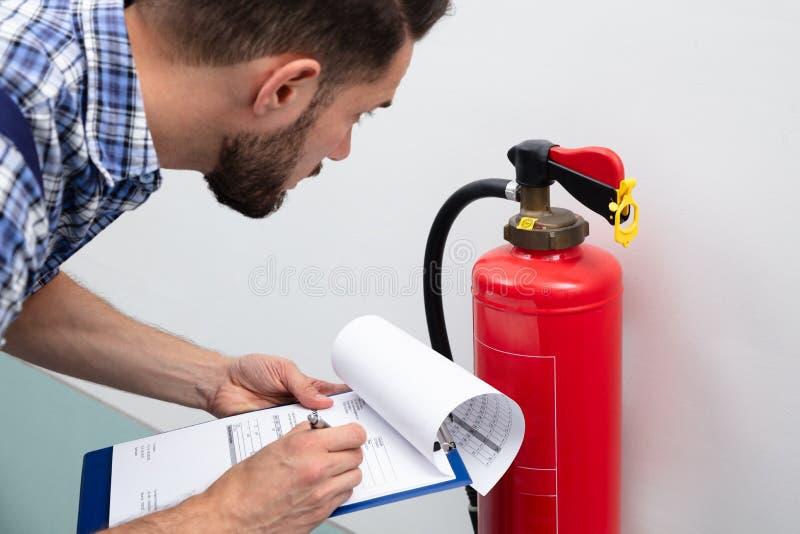 Hombre que comprueba el extintor que escribe en el documento imagen de archivo