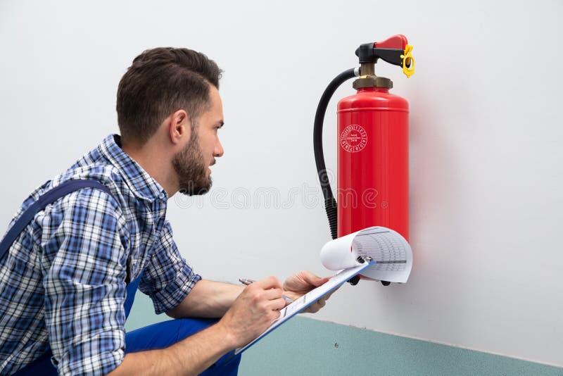 Hombre que comprueba el extintor que escribe en el documento imagenes de archivo