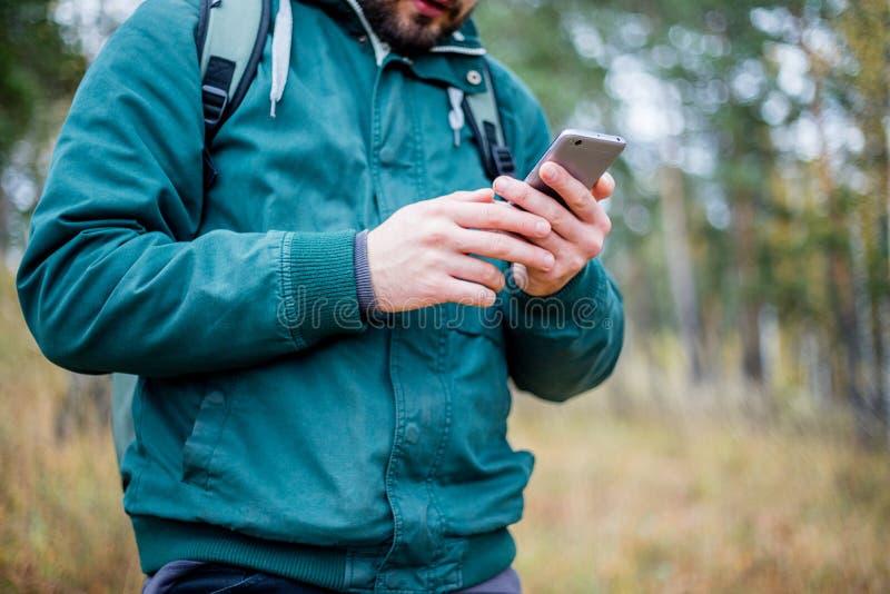Hombre que comprueba el mapa en el teléfono mientras que camina imagen de archivo