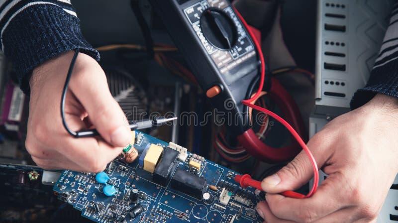 Hombre que comprueba el ordenador con un mult?metro foto de archivo libre de regalías