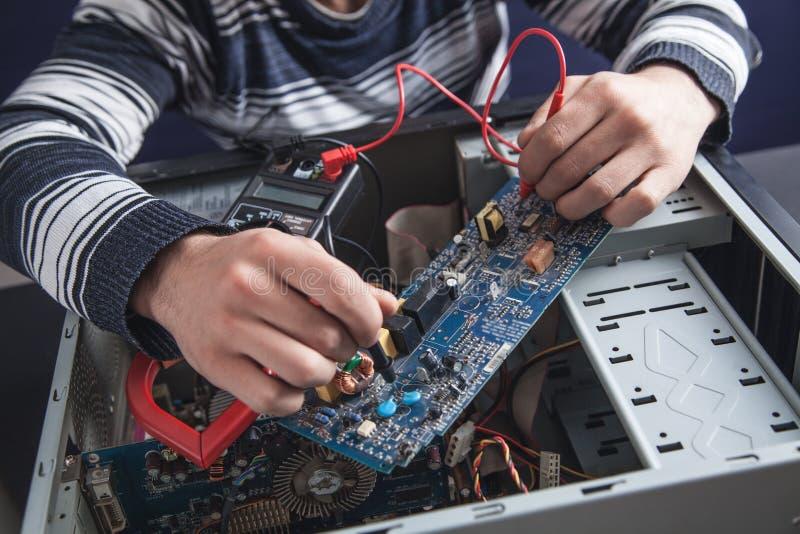 Hombre que comprueba el ordenador con un mult?metro imagenes de archivo