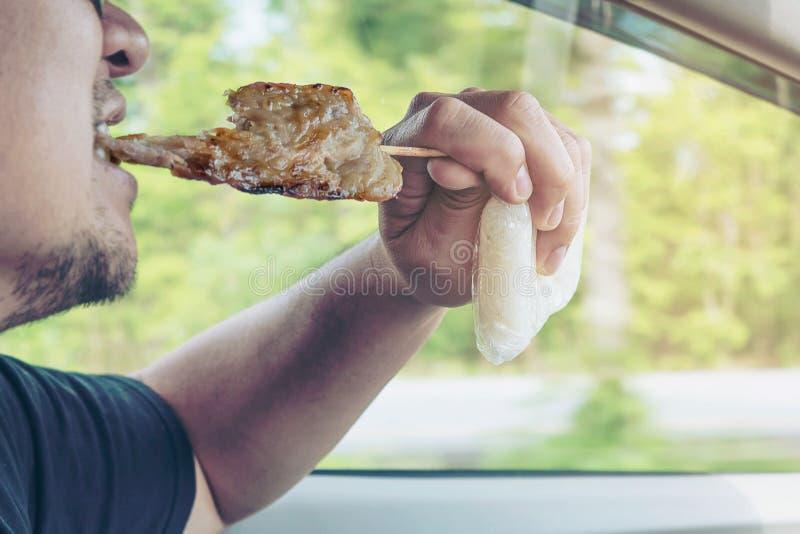 Hombre que conduce el coche mientras que come el palillo asado a la parrilla del cerdo fotos de archivo libres de regalías