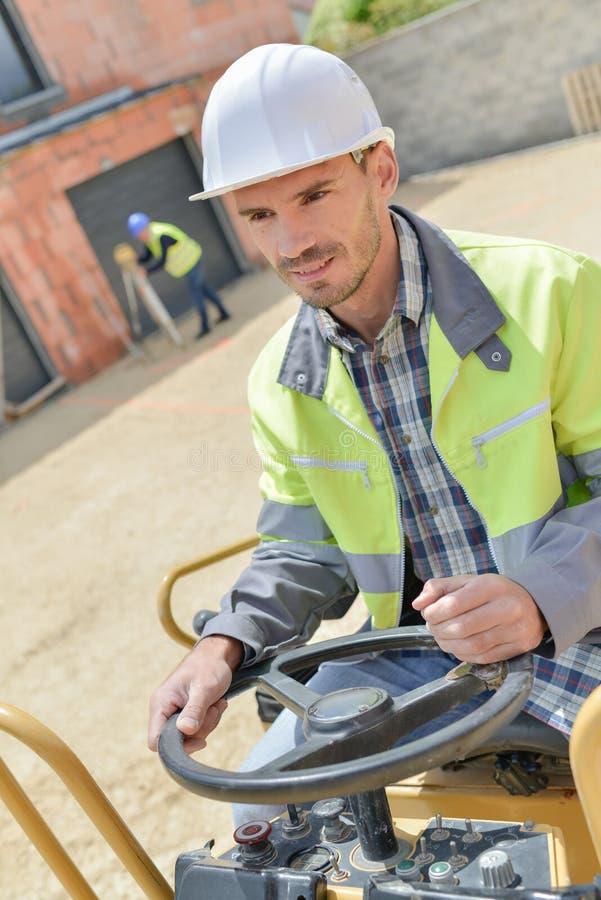 Hombre que conduce el vibrador de la taladradora en la carretera de asfalto imagenes de archivo