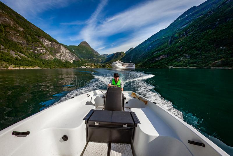 Hombre que conduce un barco de motor Fiordo de Geiranger, naturaleza hermosa Noruega Vacaciones de verano fotografía de archivo libre de regalías