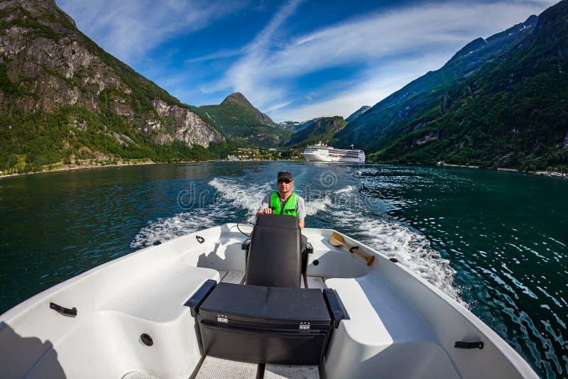 Hombre que conduce un barco de motor Fiordo de Geiranger, naturaleza hermosa Noruega Vacaciones de verano foto de archivo libre de regalías