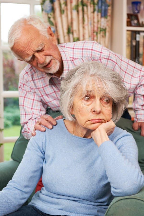 Hombre que conforta a la mujer mayor con la depresión imagen de archivo