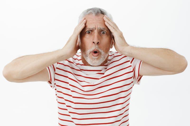 Hombre que consigue chocado y aturdido con las cosas que suceden alrededor Retrato del viejo varón ansioso intenso preguntado con foto de archivo