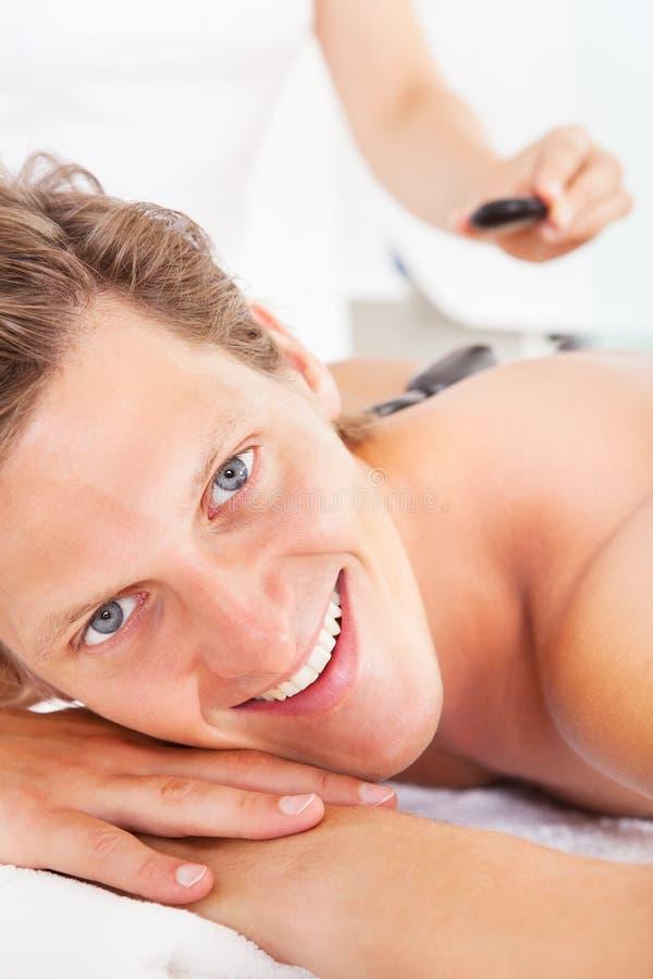 Hombre que consigue masaje de piedra caliente imagen de archivo libre de regalías