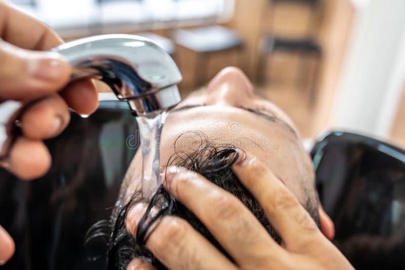 Hombre que consigue un pelo lavado en Barber Shop imagen de archivo