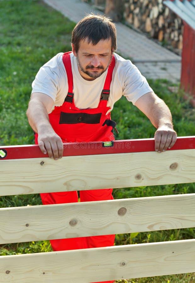 Hombre que construye la nueva cerca de madera fotografía de archivo