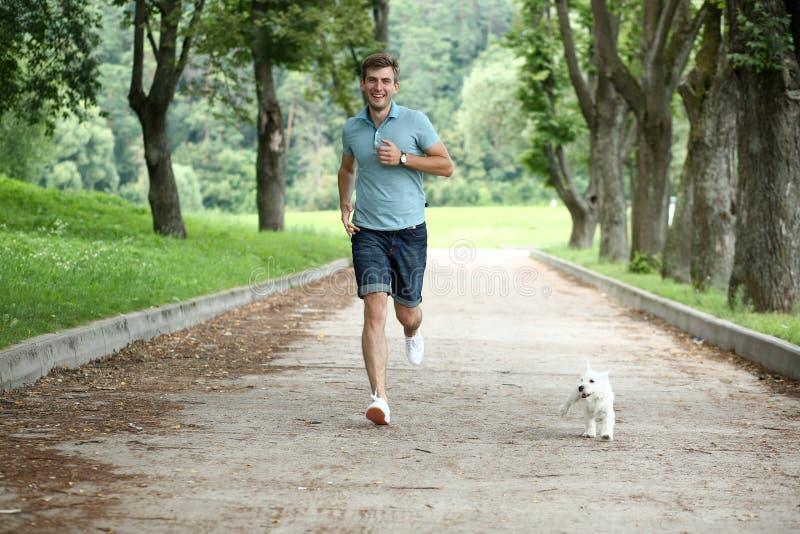 hombre que corre con su perro imagenes de archivo