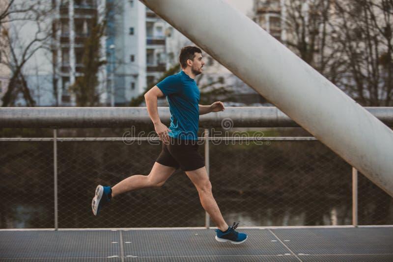 Hombre que corre rápidamente a lo largo del puente fotos de archivo