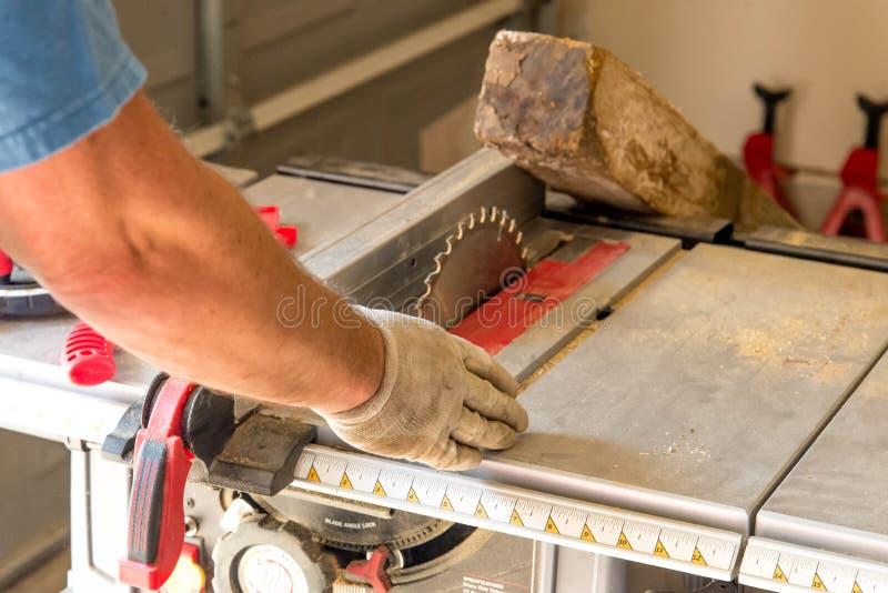 Hombre que corta 4x4 en la sierra de la tabla imágenes de archivo libres de regalías