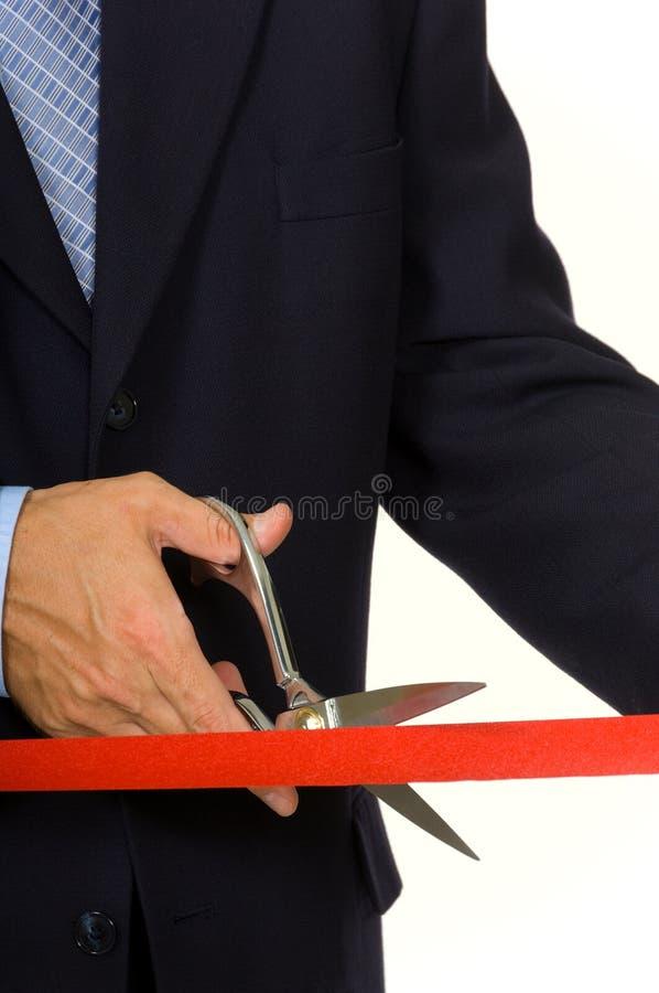 Hombre que corta la cinta roja foto de archivo libre de regalías