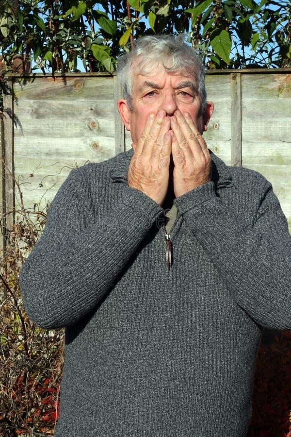 Hombre que cubre su boca con sus manos. fotos de archivo libres de regalías