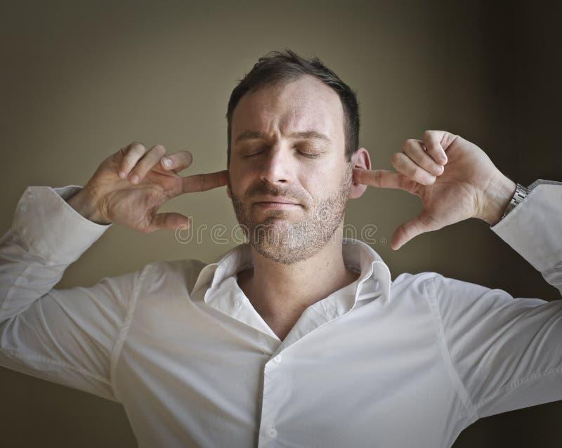 Hombre que cubre sus oídos imagenes de archivo