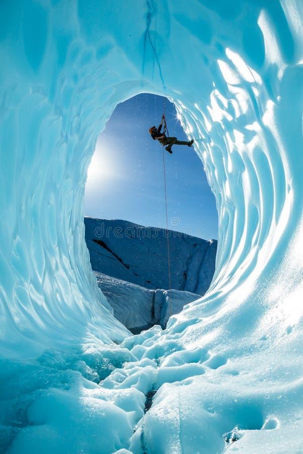 Hombre que cuelga de una cuerda dentro de la cueva de hielo grande del glaciar de Matanuska en Alaska backcountry imágenes de archivo libres de regalías
