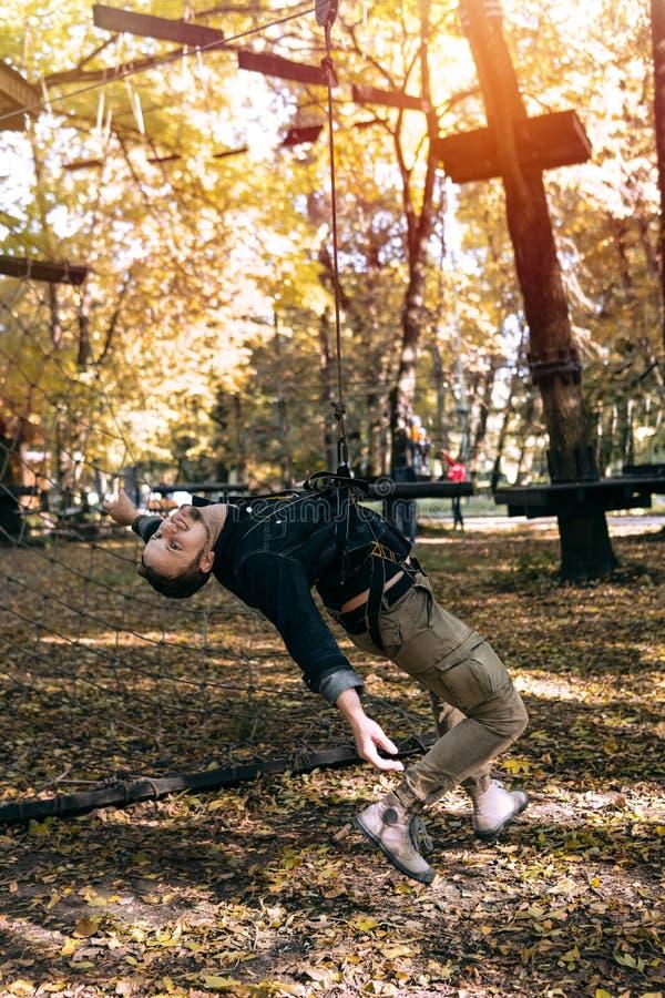 Hombre que cuelga en una cuerda de la seguridad, engranaje que sube en obstáculos de la aventura de un paso del parque en el cami foto de archivo libre de regalías