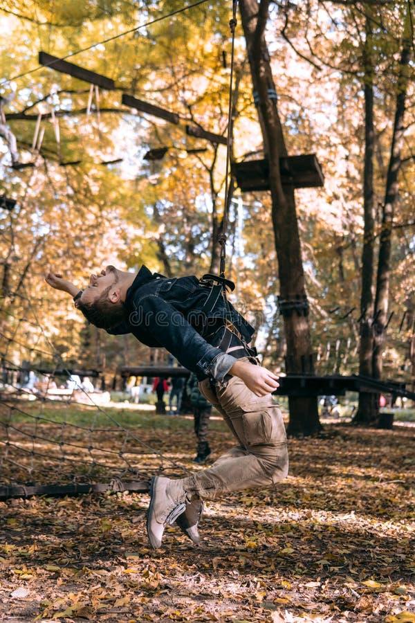 Hombre que cuelga en una cuerda de la seguridad, engranaje que sube en obstáculos de la aventura de un paso del parque en el cami imágenes de archivo libres de regalías
