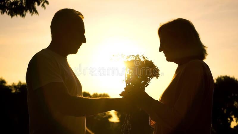 Hombre que cuida que presenta las flores a la mujer en la puesta del sol, aniversario de boda, amor imagenes de archivo