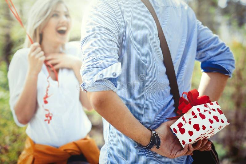 Hombre que da el regalo de la sorpresa como presente a su novia preciosa fotos de archivo libres de regalías