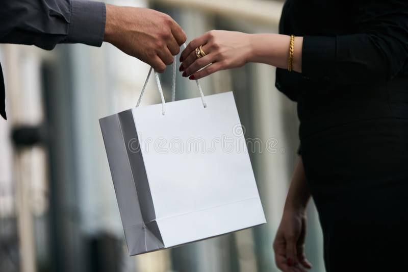 Hombre que da el regalo en bolsa de papel a la mujer, primer fotos de archivo libres de regalías