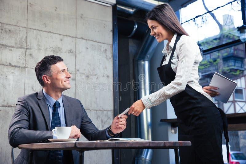 Hombre que da la tarjeta de banco al camarero de sexo femenino fotos de archivo libres de regalías