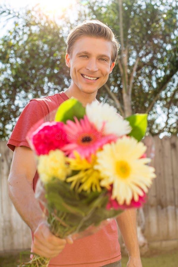 Hombre que da las flores imagenes de archivo