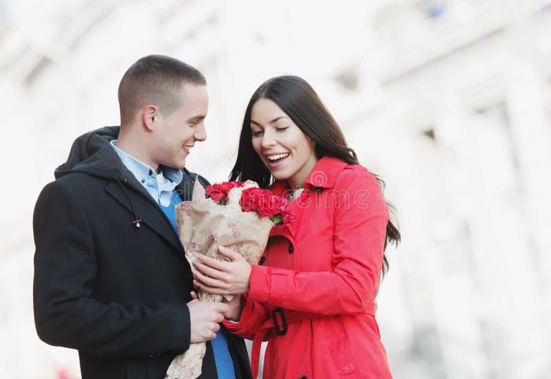 Hombre que da las flores a su novia; pares jovenes, románticos al aire libre imagen de archivo libre de regalías