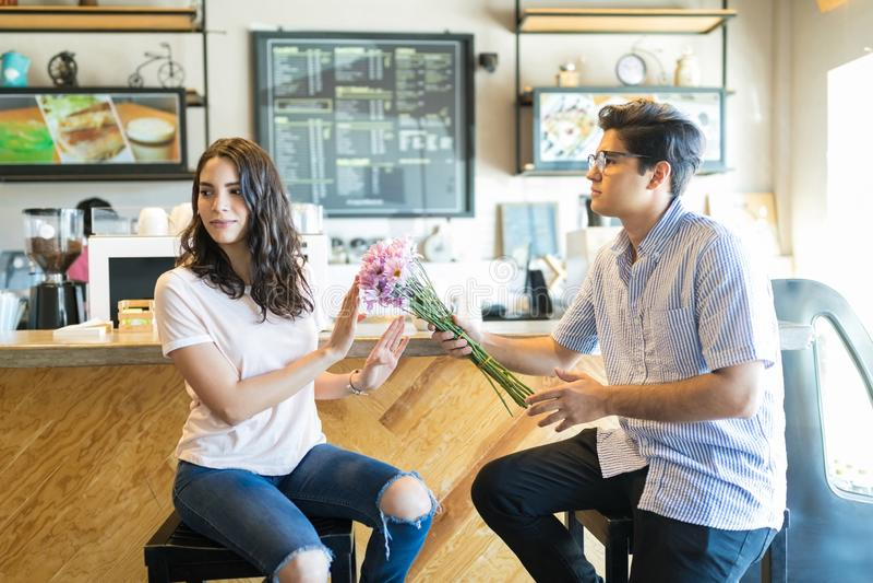 Hombre que da las flores a una mujer irritable foto de archivo libre de regalías