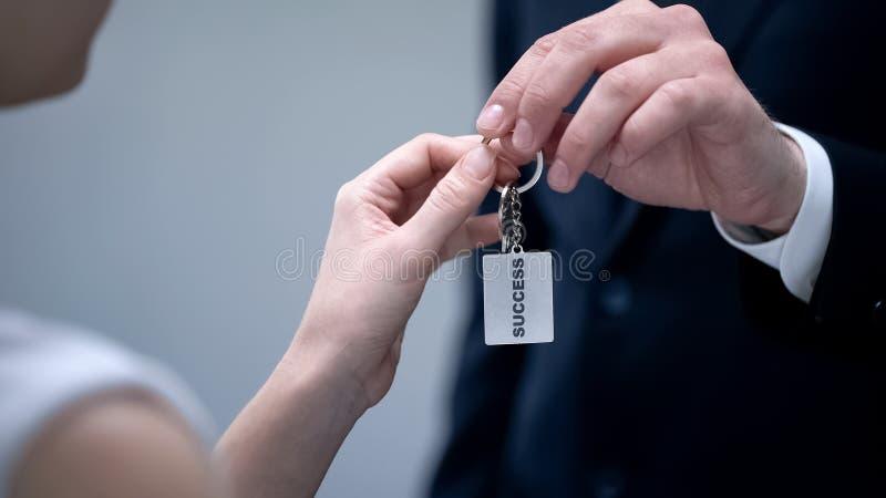 Hombre que da las llaves al éxito, extremidades secretas de la mujer para dar vuelta a sueño en el primer de la realidad fotos de archivo
