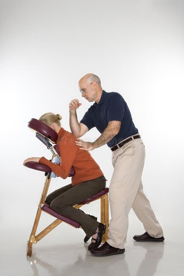 Hombre que da masajes a la mujer. imagen de archivo