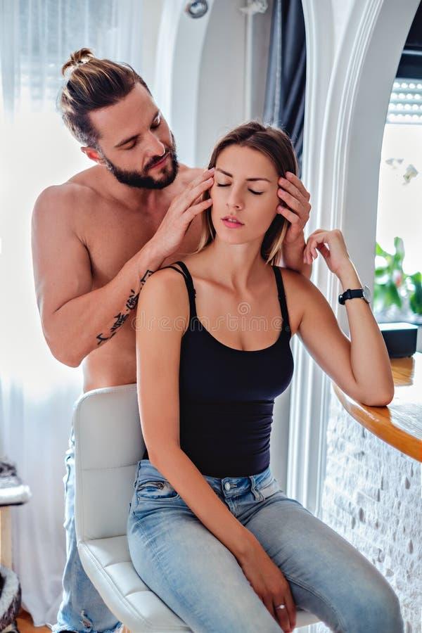 Hombre que da masajes a su girlfriend& x27; cabeza de s fotografía de archivo