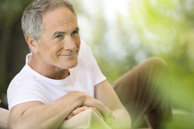 Hombre que descansa en silla de cubierta en jardín fotografía de archivo