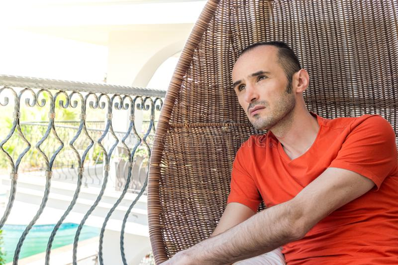 Hombre que descansa para relajarse en la silla de balanceo en un balcón fotos de archivo libres de regalías
